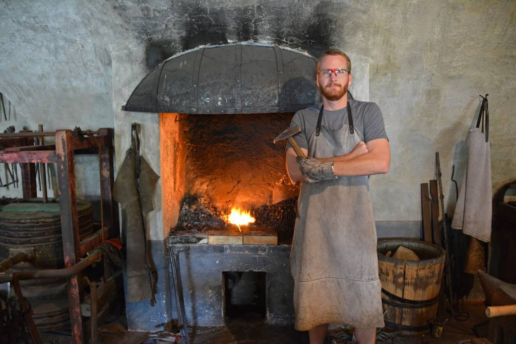 Blacksmith with hammer and forge
