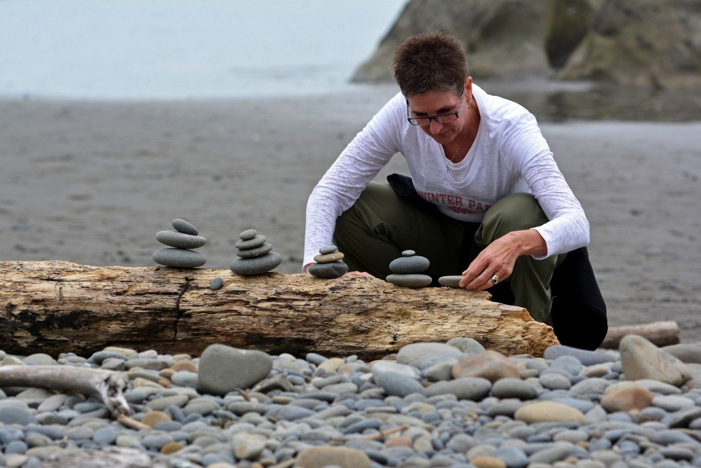 Woman stacking rocks on the beach