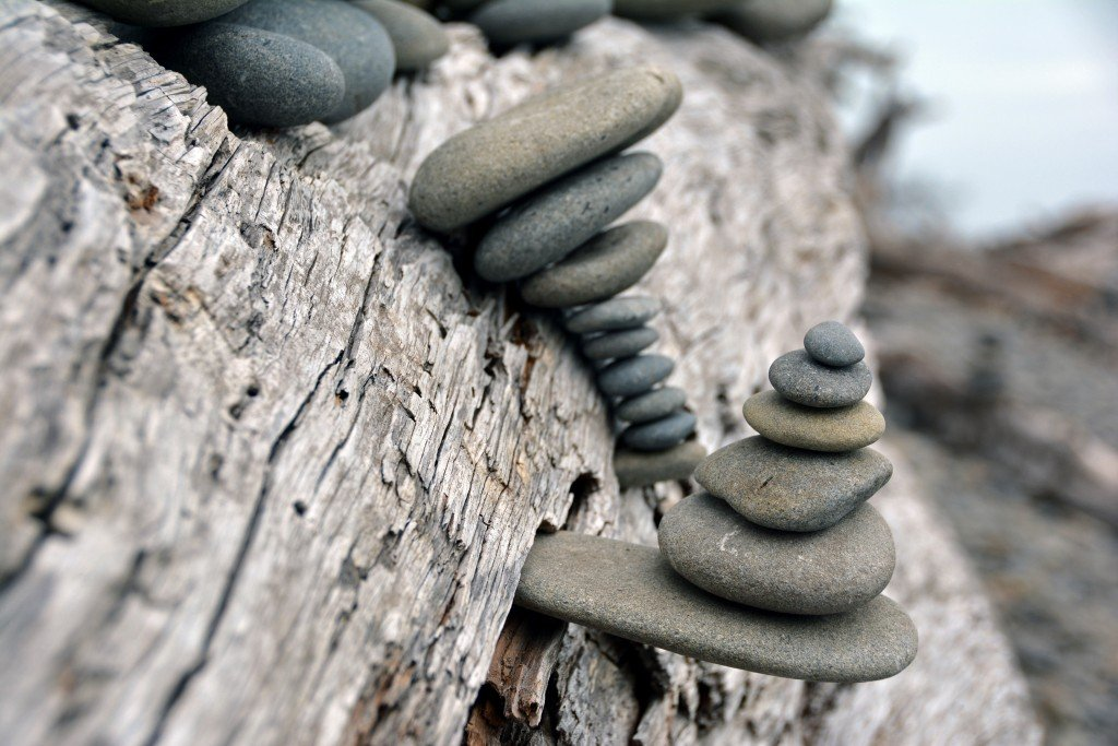 Stacked rocks on beach driftwood