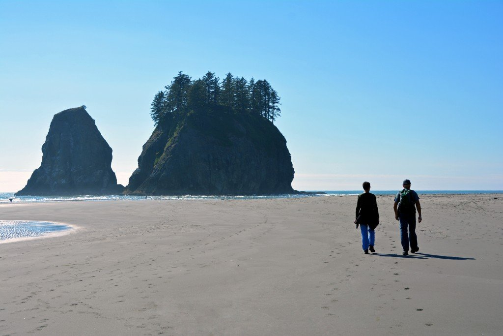 Couple walking on the beach near sea stacks